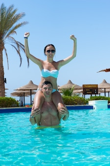 화창한 여름날 호텔 수영장에서 아쿠아 피트니스를 하는 동안 젊은 남자의 목에 앉아 있는 소녀
