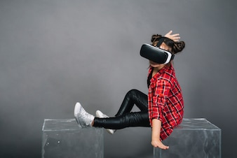 Girl sitting on transparent blocks wearing virtual reality goggles against gray background