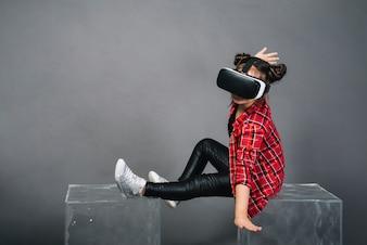 仮想現実を身に着けている透明なブロックに座っている女の子は灰色の背景に対してゴーグルします。