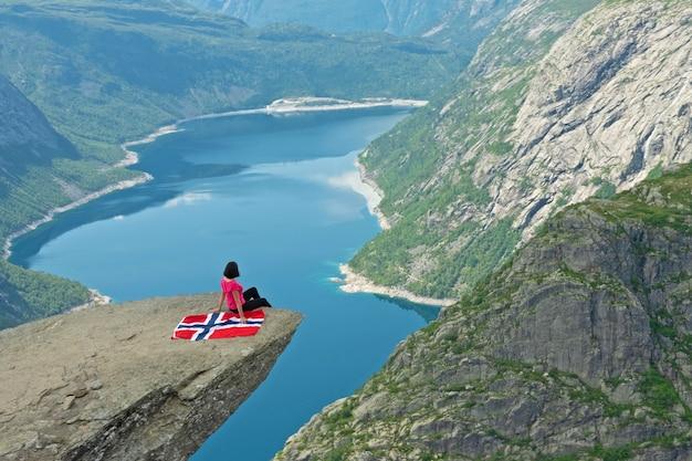 Девушка сидит на скале тролльтунга с норвежским флагом, горный пейзаж озера рингедалсватнет, норвегия.