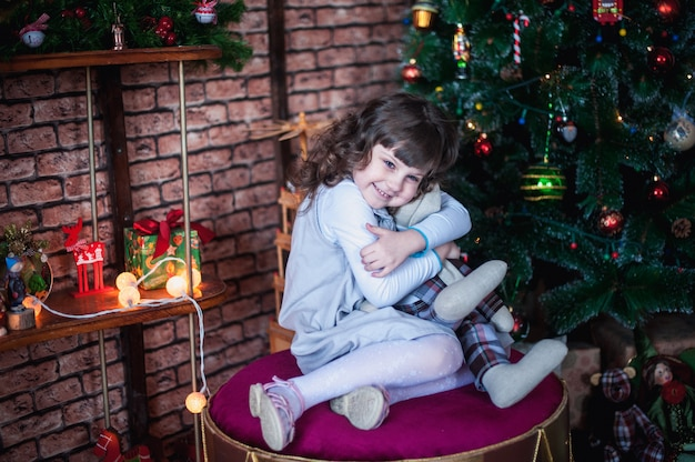 Girl sitting on ottoman in front of tree and hugging toy bunny