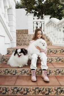 Девушка сидит на открытом воздухе со своими собаками