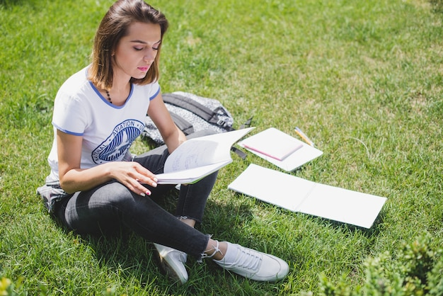 Girl sitting in park holding notebook reading