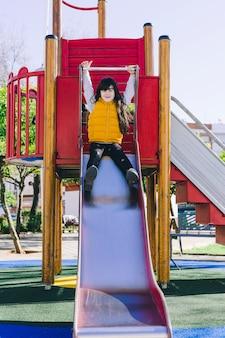 Girl sitting on playground slide