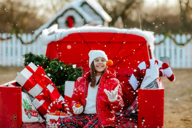 Girl sitting in red retro car with christmas decor and juggling tangerines