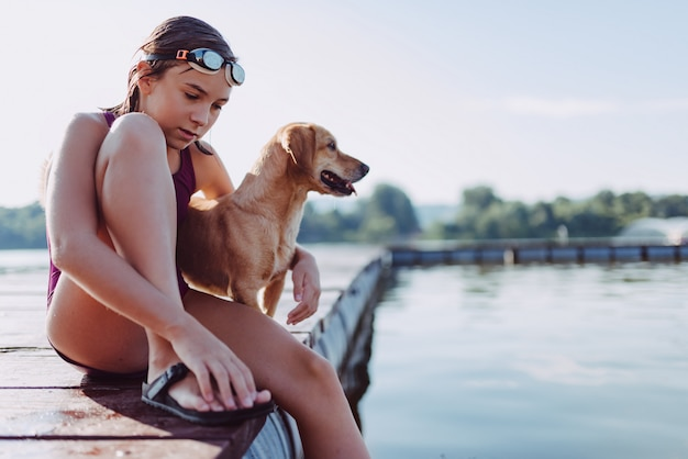 Girl sitting on the river dock with her dog