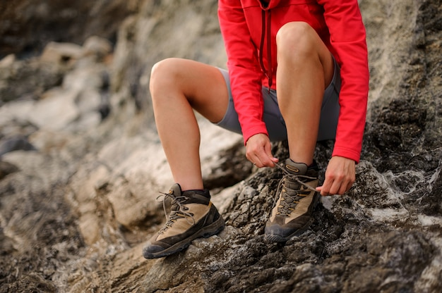 Girl sitting on the rock and tie shoelaces