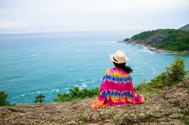 The girl sitting at the rocks looking at the beautiful blue sea