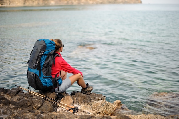 Girl sitting on the rocks with hiking backpack and walking sticks