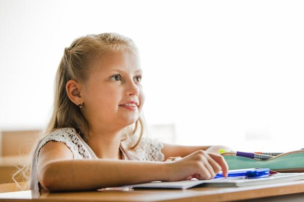 Ragazza seduta alla scrivania scuola sorridente