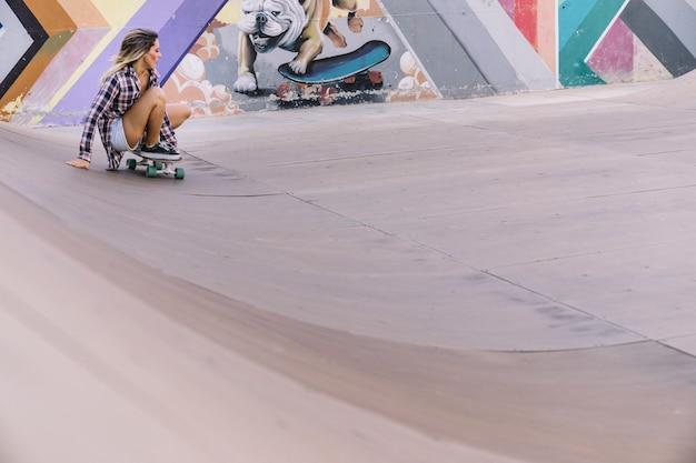 Ragazza seduta sullo skateboard