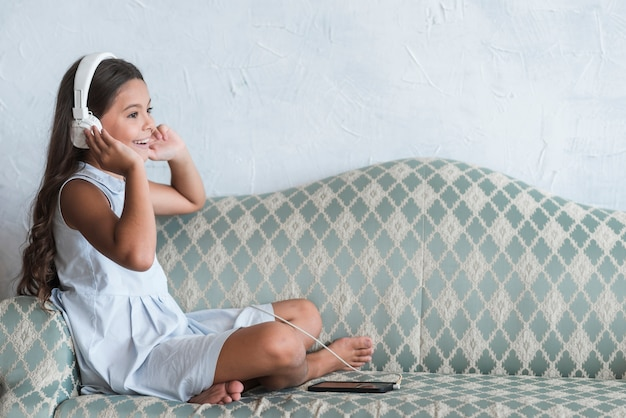 A girl sitting on sofa listening music on headphone attached to cell phone