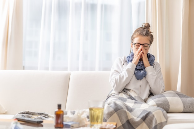 Girl sitting on a sofa and sneezing because of cold and fever.