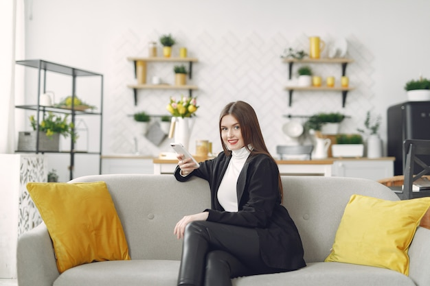 Girl sitting on the sofa and use the phone