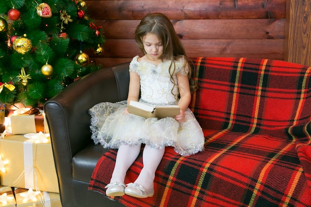 Girl sitting on a sofa with a book in her hands.