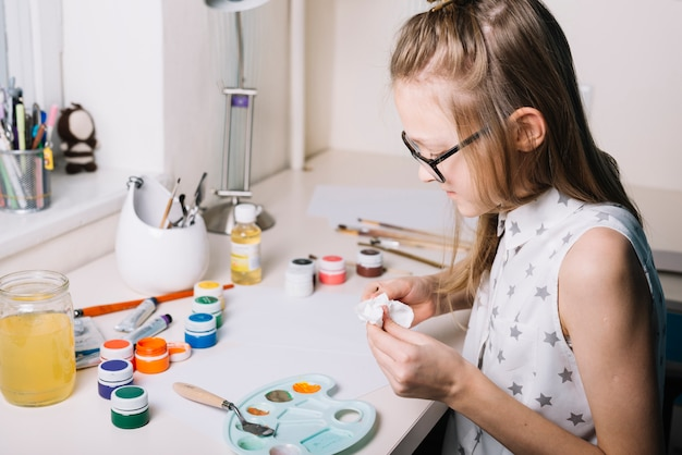 Girl sitting at table with gouache cans and palette