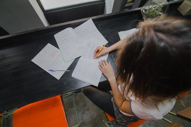 Girl sitting at table writing
