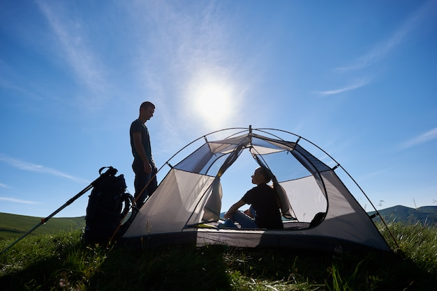 Girl sitting in the tent and the guy stands around and looks at her on the background of blue sky with bright sunshine and green hills