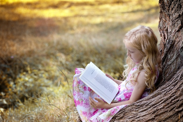 Girl sitting under a tree in the forest and reading a book