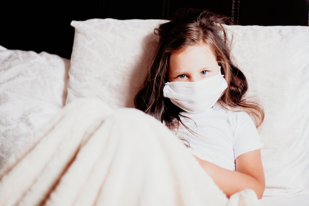 Girl sitting in a white mask on the bed in the bedroom, self-isolation for a cold, the second wave of viruses.