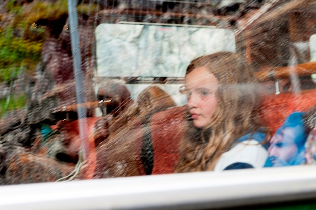 Girl sitting at a window on a tour bus, norway