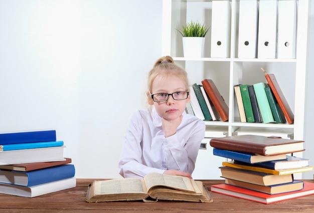 本をテーブルに座っている女の子