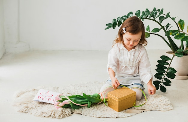 Girl sitting with gift box and greeting card