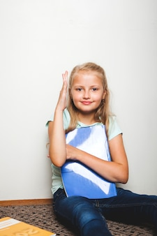 Girl sitting with notebook holding hand up