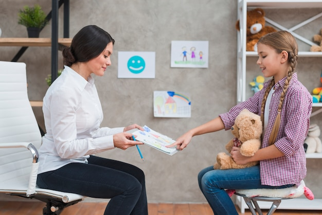Girl sitting with teddy bear pointing at the drawing paper shown by her female psychologist