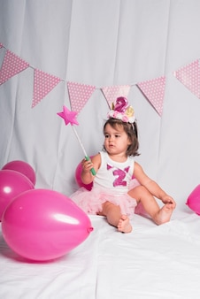 A girl sitting with a wand and pink balloons on white.