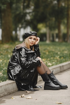 座っている女の子。黒いコートを着た女性。黒い帽子をかぶった金髪。