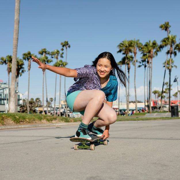 女の子のスケートボード、ロサンゼルスでの楽しいアウトドアスポーツ活動
