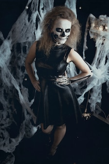 Girl skeleton witch posing in the webs, halloween. witch is preparing for the holiday nights of the dead