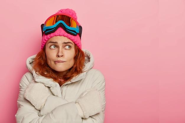 女の子のスキーヤーは寒さを感じ、唇を震わせて噛み、暖かい冬のアウターを着て、暖めようとし、ピンクのスタジオの壁に立ち向かい、スペースをコピーします
