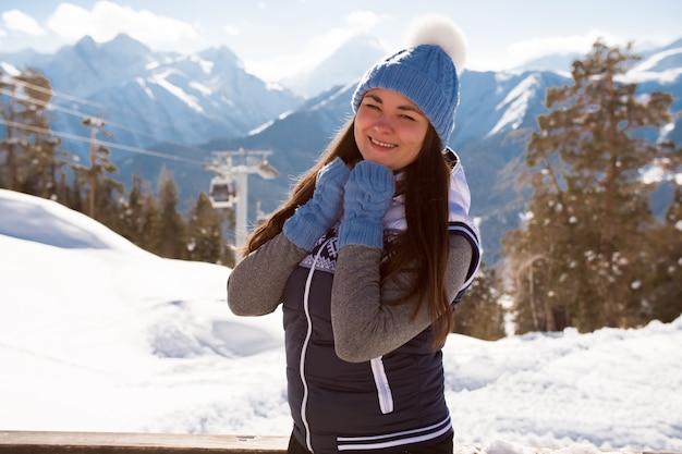 スキーリゾートのカフェのベランダのインテリアでポーズをとって丘の上の少女スキーヤー