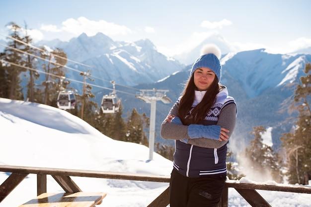 スキーリゾートの山の上のカフェのベランダの内部でポーズをとる丘の上の女の子スキーヤー