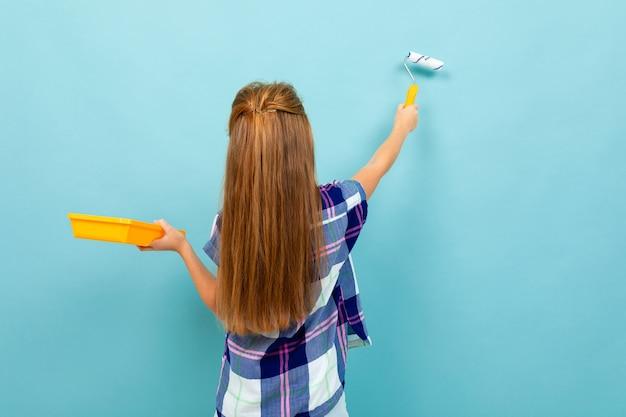 Девушка умело красит голубую стену.