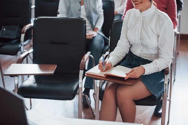 Girl in skirt is smiling. group of people at business conference in modern classroom at daytime