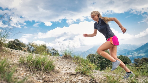 Girl skyrunner uphill on a running trail