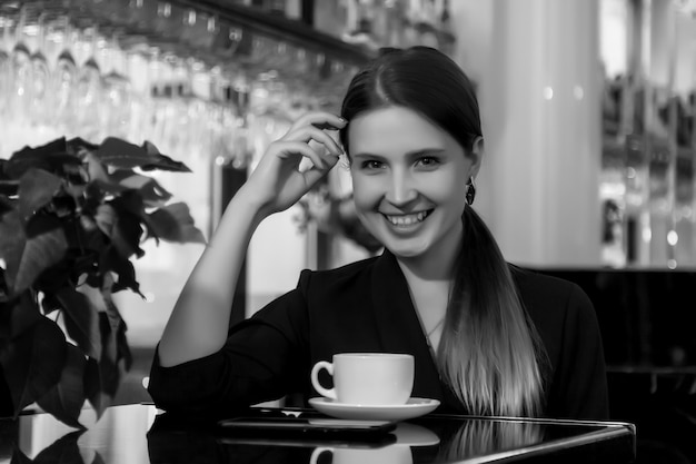 Girl of slavic appearance in bar, cafe or restaurant with white cup. female shows emotion. young charming woman is sitting at bar and drinking coffee or tea in her free evening time