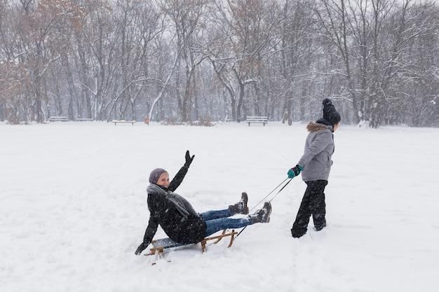 Girl sledding her mother at winter park