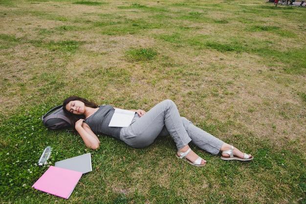 Ragazza che dorme sull'erba nel parco
