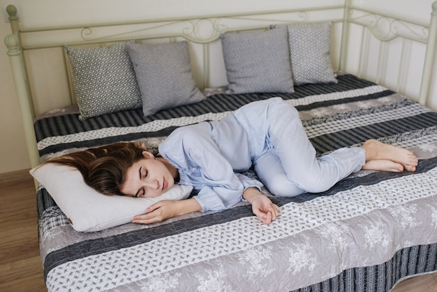 The girl sleeping in her pajamas on the bed in her room. stylish gray-white interior.