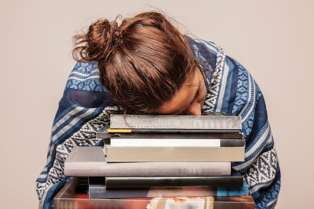 Girl sleeping on pile of books