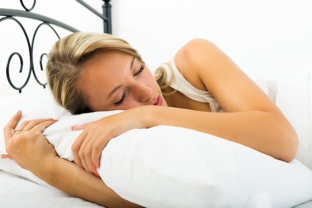 Ragazza che dorme con un cuscino bianco