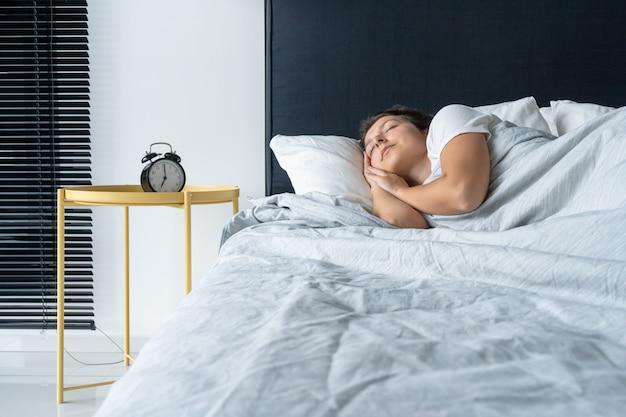The girl sleeps next to the alarm clock. time to wake up. on the wake-up clock 7 a.m. deep sleep.