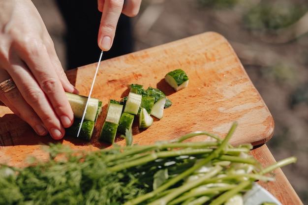 La ragazza affetta le verdure sul bordo e prepara un'insalata sulla natura. giornata di sole e cucina. vista ravvicinata.
