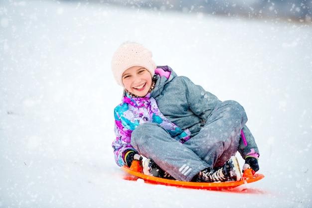 Girl sliding down the hill on saucer sled