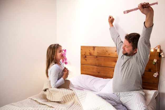 Girl smelling a flower while her father raises her arms