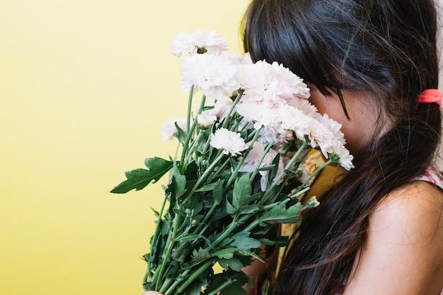 Ragazza che sente l'odore dei fiori
